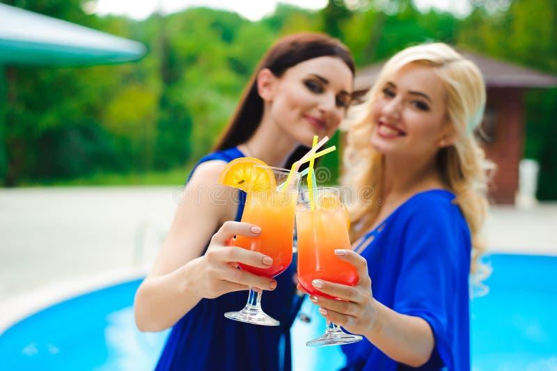 比基尼泳装的美丽的性感的妇女喝鸡尾酒一会儿的放松在游泳场 免版税图库摄影