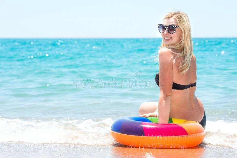 比基尼泳装的美丽的性感的妇女有可膨胀的圈子的坐海滩 ï ¿ ¼ï ¿ ¼ 库存图片