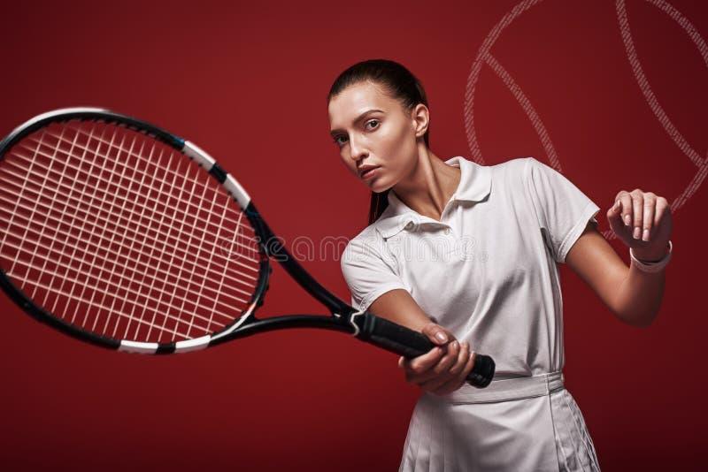 比赛、集合,比赛年轻网球员身分被隔绝在与球拍的红色背景和球 免版税库存图片