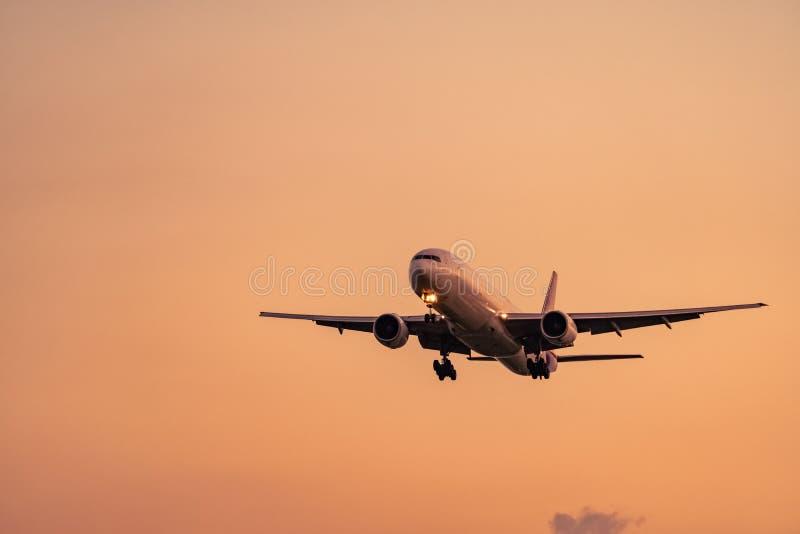 民航 客机着陆在有美丽的日落天空和云彩的机场 到来飞行 飞机飞行 库存照片