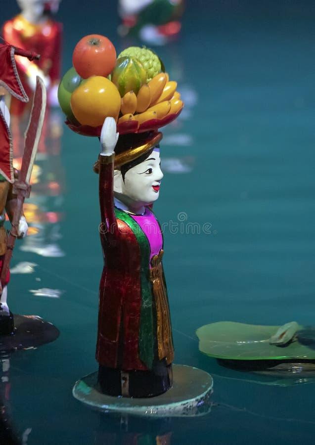 水运载果子的篮子在她的头的木偶妇女在Thang长的水木偶剧院,河内,越南 库存照片