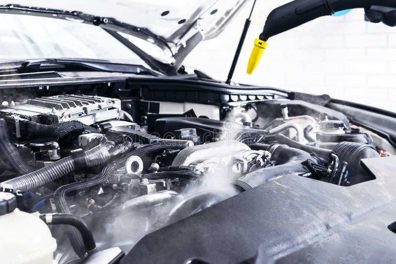 汽车详述 汽车洗涤的清洁引擎 使用热的蒸汽的清洗的汽车 热的蒸汽引擎洗涤物 软的照明设备 汽车washman wor 库存照片