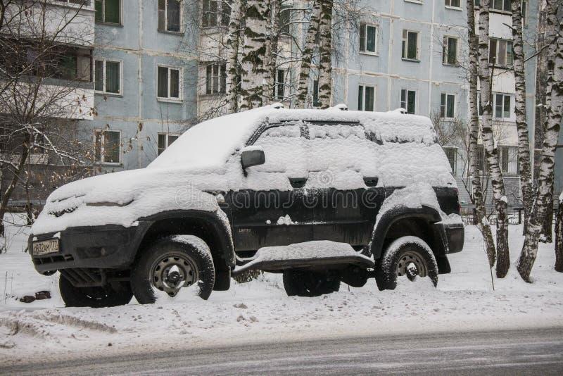 汽车,盖用雪厚实的层数,在围场住宅房子在provilcial镇 免版税库存照片