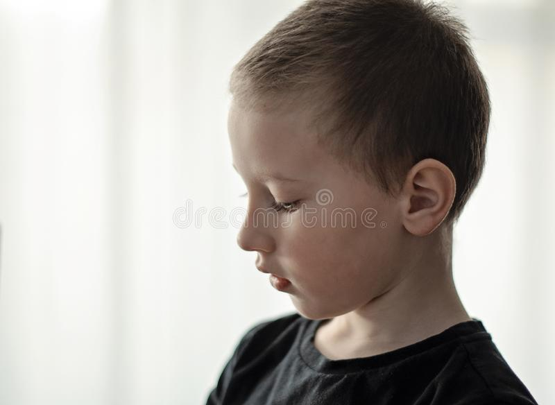 沮丧的年轻幼儿园男孩特写镜头画象认为黑的T恤杉的看下来和 有哀伤的面孔的不快乐的单独孩子 免版税库存照片