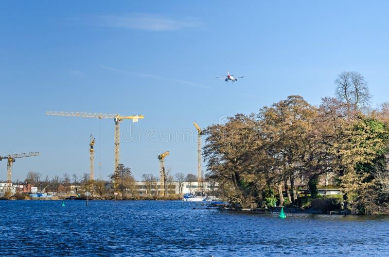 河哈维尔,海岛Eiswerder,从朝向机场柏林特赫尔的一个最近被架设的区和飞机的塔吊 库存照片