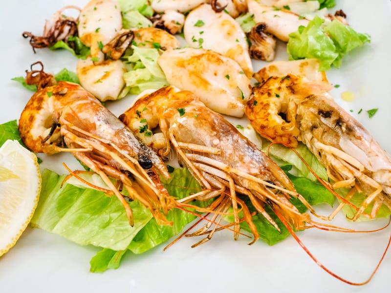 油煎的大虾和乌贼在白色板材关闭  免版税图库摄影
