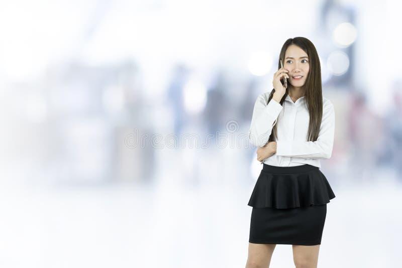 沟通与手机的亚裔女商人办公室工作者 库存图片