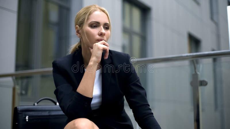沉思女实业家坐长凳,担心关于麻烦在工作,重音 免版税库存图片