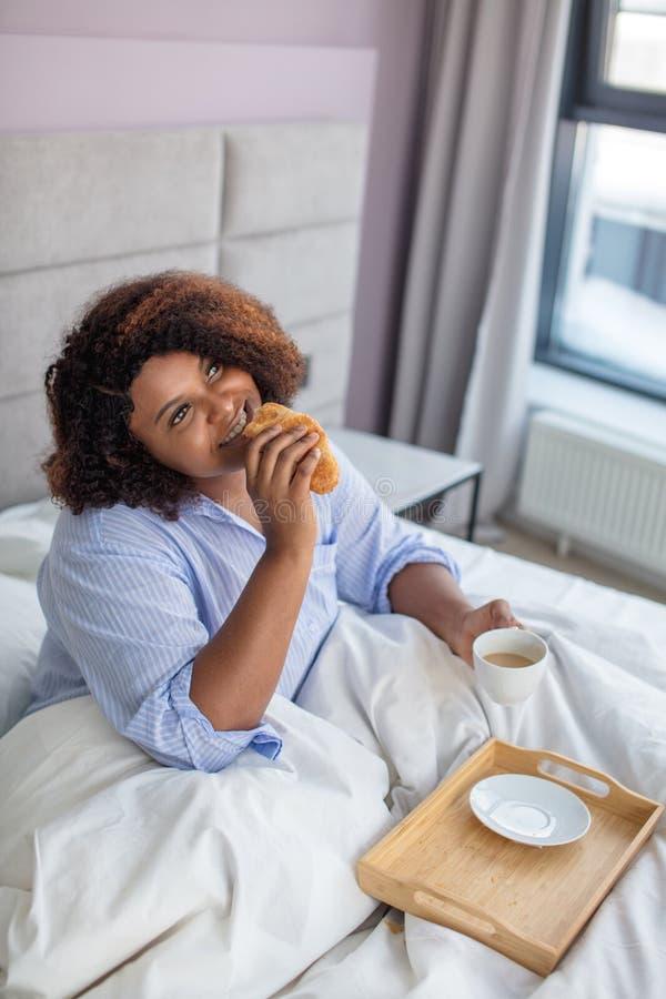 沉思愉快的妇女吃早餐在床 免版税图库摄影