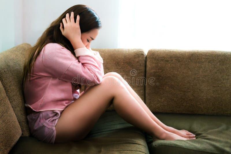 沙发的沮丧的年轻女人在家 免版税库存图片