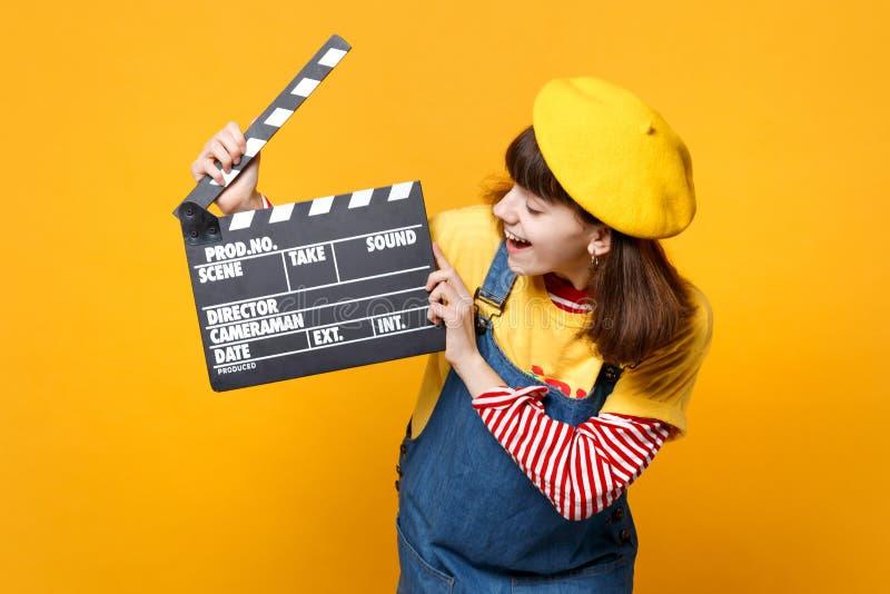 法国贝雷帽的,看在经典黑电影制作clapperboard的牛仔布sundress笑的女孩少年被隔绝  免版税库存照片