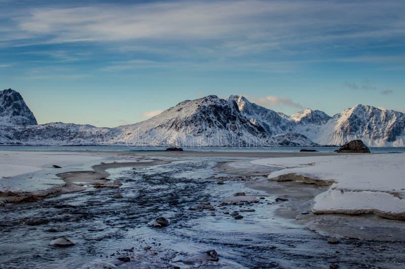 流动下来到在罗弗敦群岛海岛上的Haukland海滩的河在冬天 免版税图库摄影