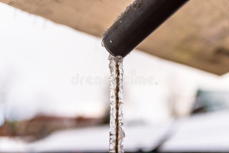 流经从屋顶的冻水有串里面的塑料管子 免版税库存图片