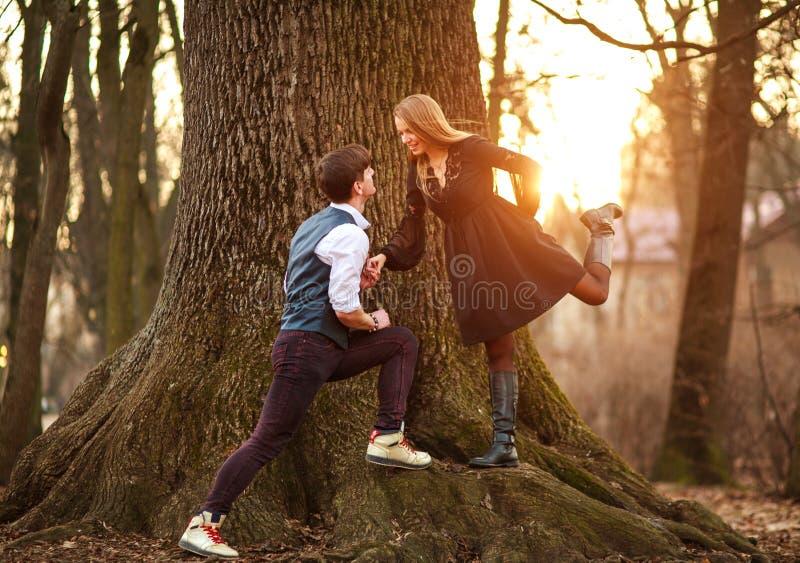 浪漫年轻夫妇一起愉快地获得乐趣在森林城市公园在日落 免版税库存照片