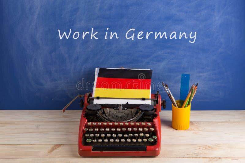 海外工作概念-德国的打字机、有文本& x22的旗子在桌上的和黑板;工作在德国 库存图片