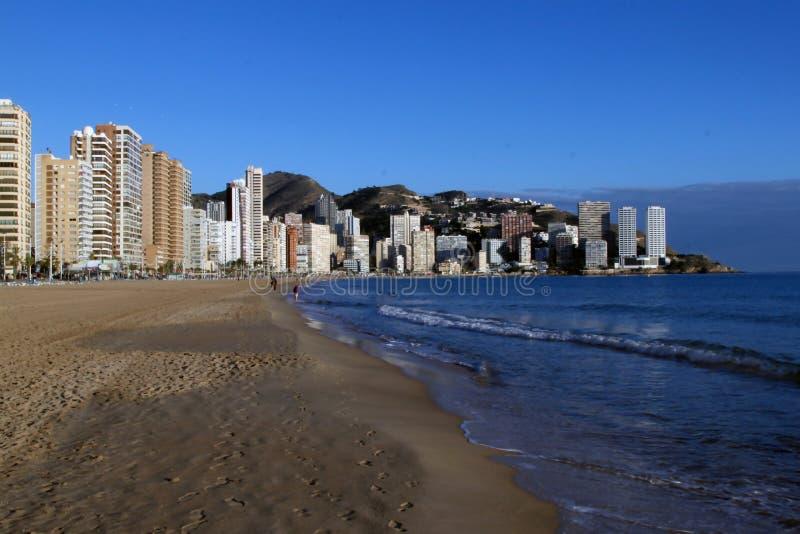 海滩和高房子反对山背景和在地中海,西班牙的岸 免版税库存照片