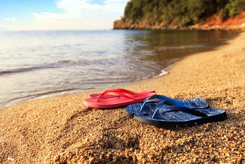 海滩拖鞋在石头说谎在透明海附近 库存图片