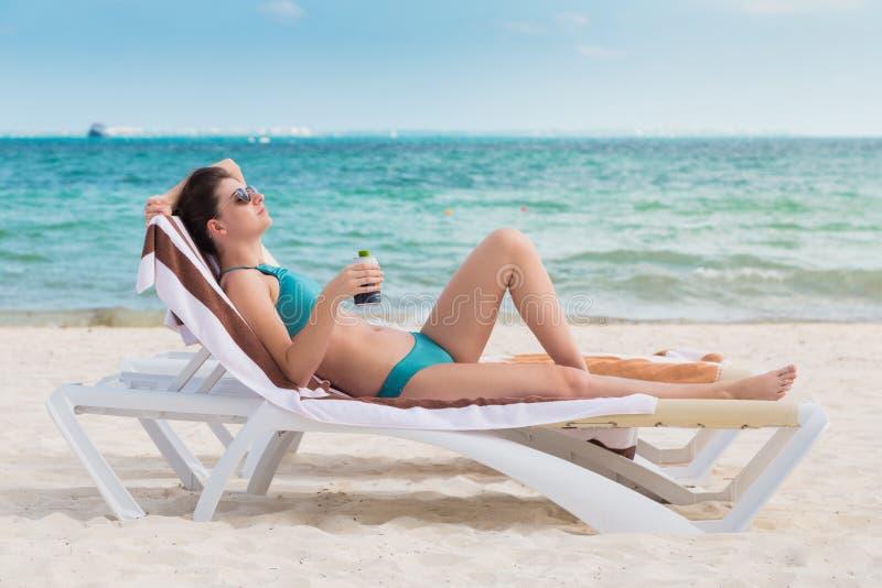 海滩睡椅的一名可爱的年轻深色的妇女喝在一个海滩的冰镇啤酒在墨西哥 图库摄影