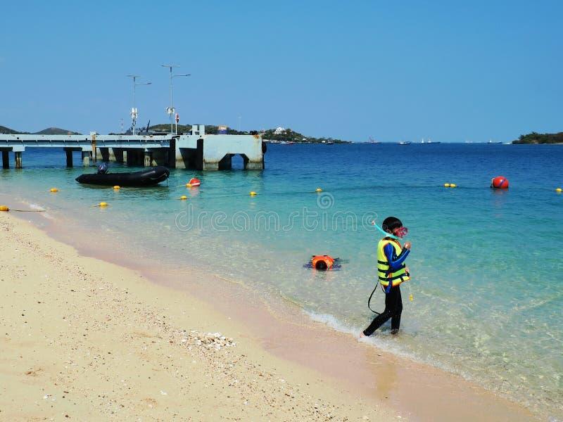 海滩的一个男孩 人是潜航的惯例在海洋 口岸是蓝色的 山是场面后侧方  水是蓝色的 图库摄影