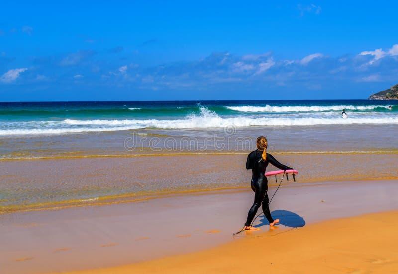 海滩的年轻女性冲浪者 免版税库存图片