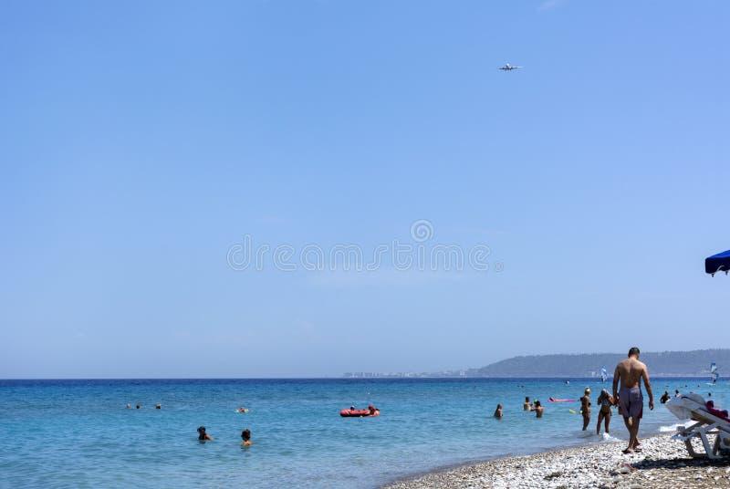 海滩,爱琴海,海滩的人们,人游泳在海,在天空的飞机,罗得岛海岸 免版税库存图片