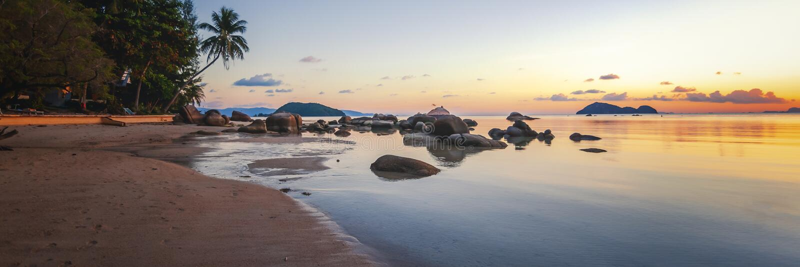 海日落震动在天空蔚蓝背景的海滩 秀丽晚上日出 海滩晃动含沙 免版税图库摄影