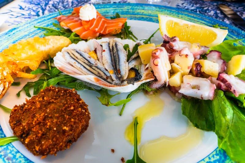 海鲜盘混合了鱼,章鱼沙拉,油煎的红色虾,用橄榄油晒干的鲥鱼 库存照片