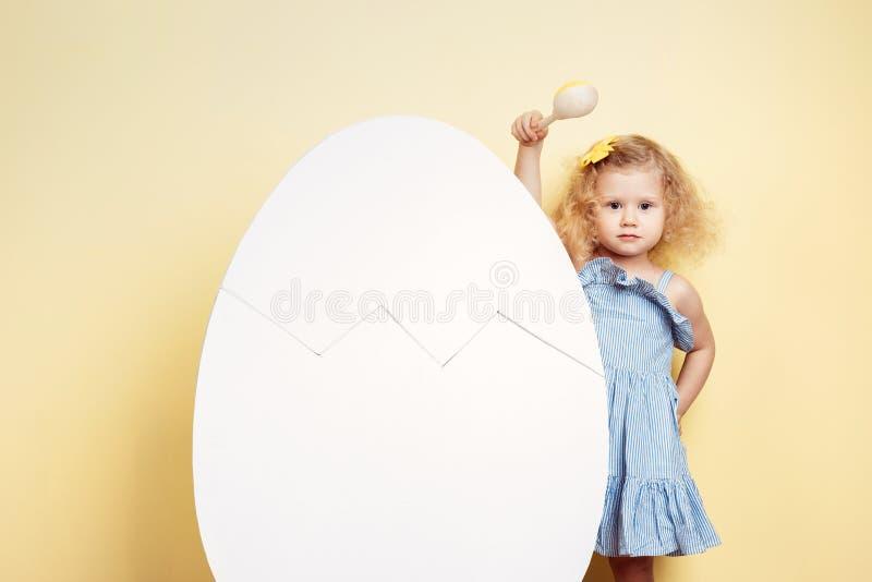 浅兰的礼服的迷人的小卷曲女孩在黄色墙壁背景的大白鸡蛋旁边站立  免版税图库摄影