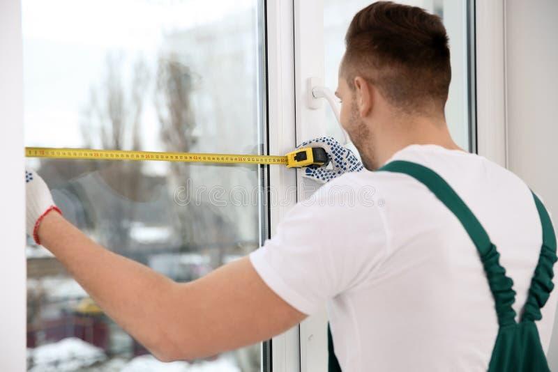 测量塑料窗口的建筑工人 专业设施 免版税库存照片