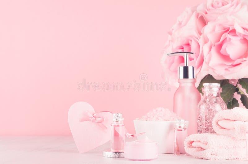 浴、温泉-精油,腌制槽用食盐、奶油、液体皂、毛巾、心脏和桃红色玫瑰的化妆用品产品在精美桃红色 库存照片
