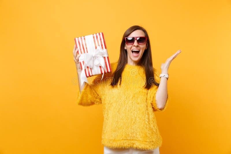 涂手的红色镜片的庆祝愉快的妇女拿着有礼物礼物的红色箱子享受假日被隔绝  库存图片