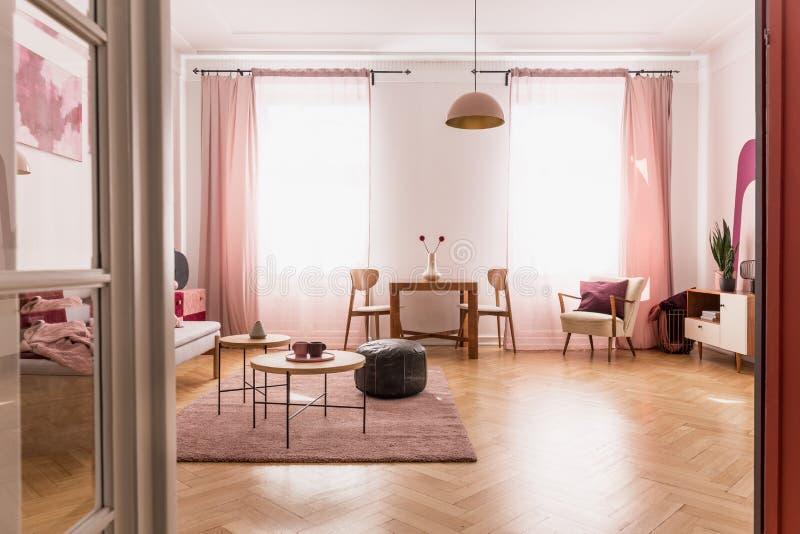 淡粉红的客厅内部在经济公寓住宅里,与拷贝空间的真正的在地板上的照片在空的白色墙壁上和木条地板 免版税库存图片
