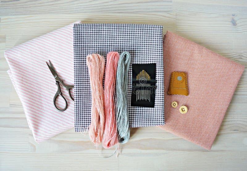 淡色羊毛刺绣螺纹、针、棉织物、减速火箭的剪刀、木按钮和皮革顶针 免版税图库摄影