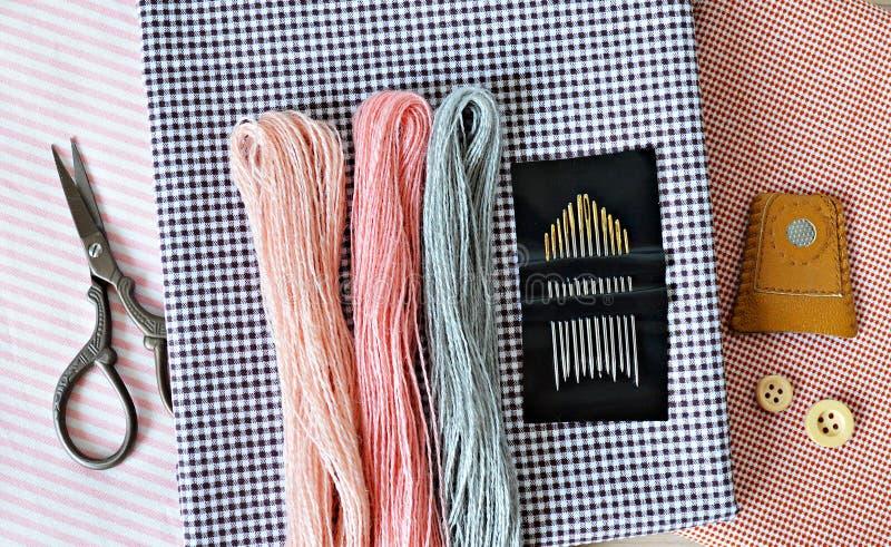 淡色羊毛刺绣螺纹、针、棉织物、减速火箭的剪刀、木按钮和皮革顶针 免版税库存图片