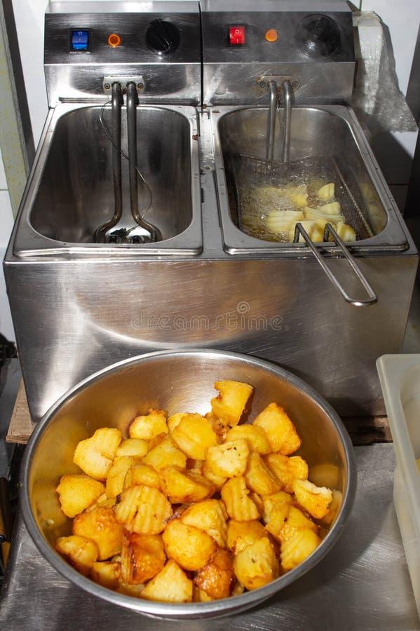 深炸锅和油煎的土豆与切片土气在餐馆,厨房 图库摄影