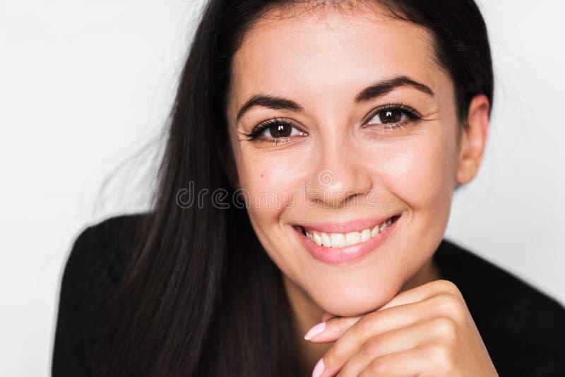 深色的逗人喜爱的妇女接近的画象有美好和健康暴牙的微笑的,与手面孔 免版税库存照片