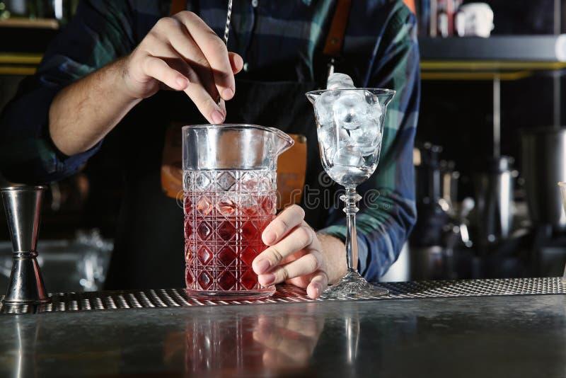 混合酒精鸡尾酒的男服务员在柜台在夜总会 免版税库存图片