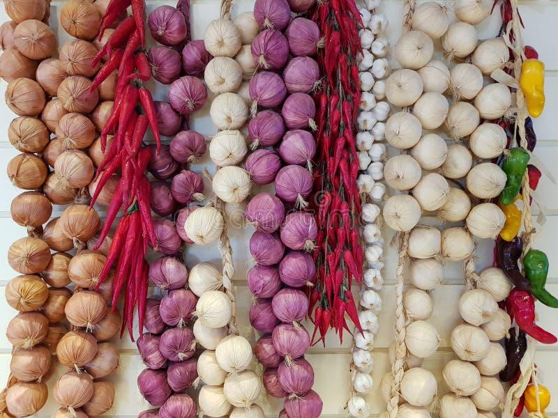 混杂的草本辣椒、葱和大蒜在白色木背景垂悬 在倾吐的餐馆沙拉的主厨概念食物新鲜的厨房油橄榄 免版税库存照片