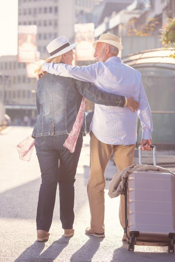 游人愉快的快乐的资深夫妇有走在街道上的地图和城市指南的 图库摄影