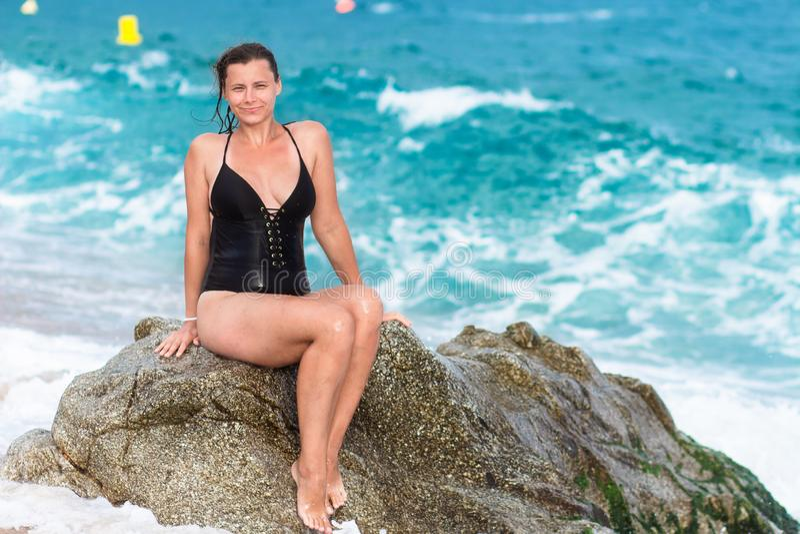 游泳衣的湿妇女坐在海滩的岩石 库存照片