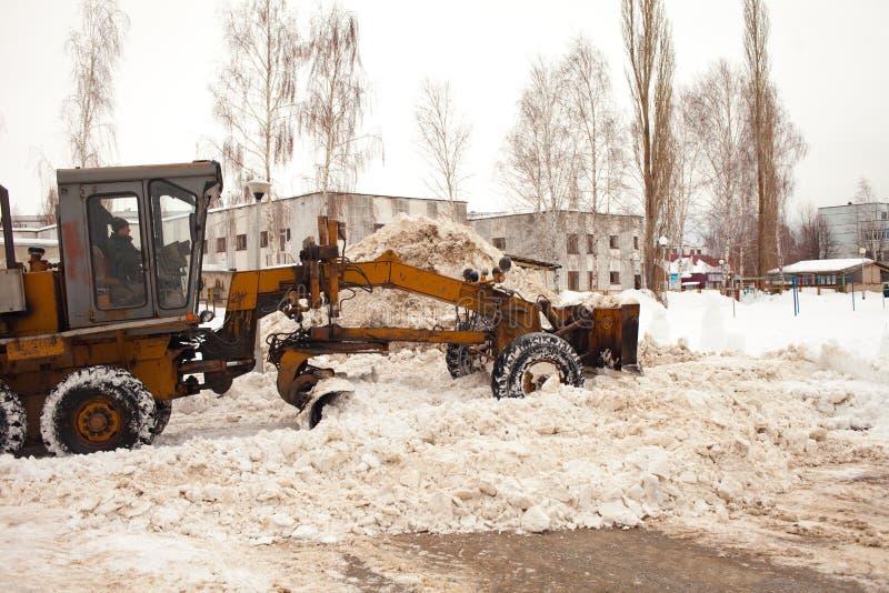 清除的雪在俄罗斯 平地机在以后扫清道路大雪 拖拉机在庭院里多层清除路 图库摄影