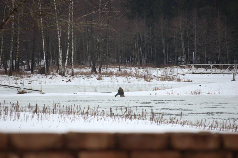 渔夫坐一冻结湖和钓鱼 冷气候在冬天 在森林湖的雪 爱好活跃人的休息 库存图片