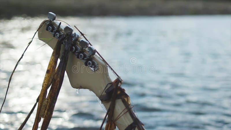 湿吉他脖子用垂悬的海带和在迷离黑暗的河背景的下跌的水下落背面图  股票 关闭 图库摄影