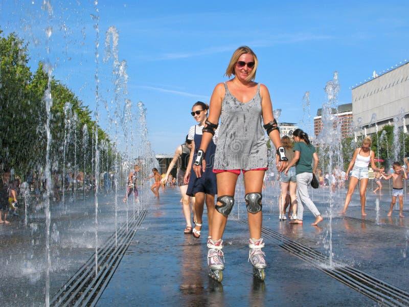 溜冰鞋的女孩,微笑,酷暑,飞溅水 免版税库存照片