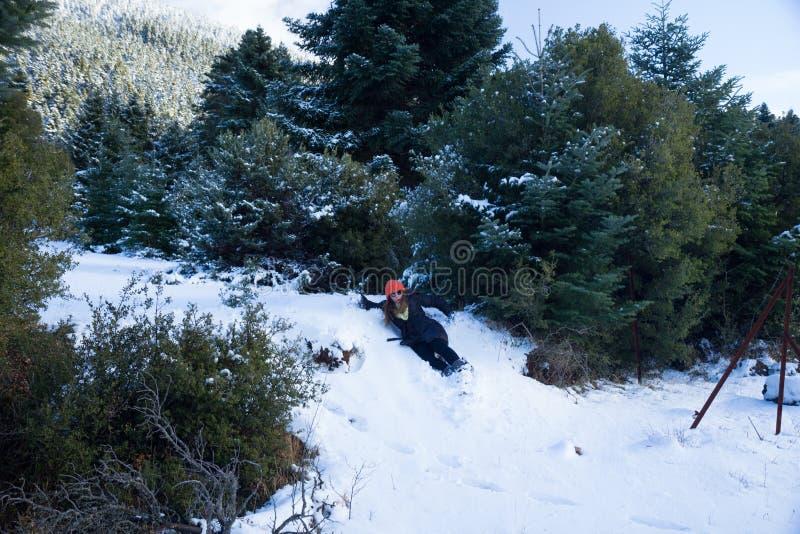 滑下来在一个小多雪的山坡的女性佩带的冬季衣服,在冷杉木之间 库存图片