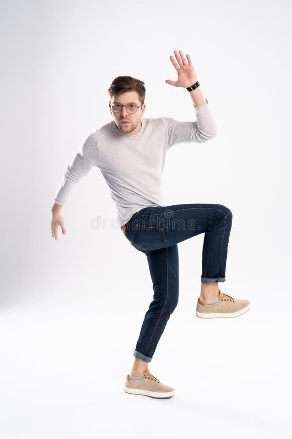 滑稽的人30s全长照片偶然T恤杉和牛仔裤跳跃的被隔绝在白色背景 库存图片