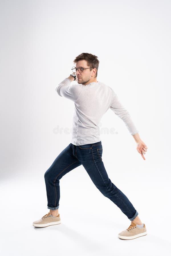 滑稽的人30s全长照片偶然T恤杉和牛仔裤跳跃的被隔绝在白色背景 库存照片