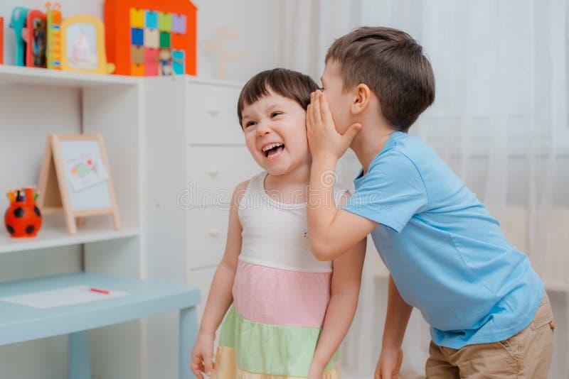 滑稽的孩子、兄弟和姐妹是朋友耳语并且笑 库存照片