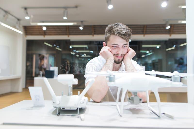 滑稽的年轻人看一quadcopter在一家轻的技术商店 购买寄生虫在电子商店 图库摄影