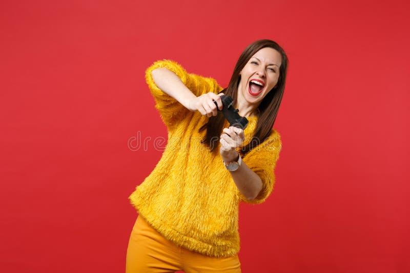 滑稽的笑的年轻女人画象打与控制杆的黄色毛皮毛线衣的电子游戏隔绝在明亮的红色 免版税库存照片